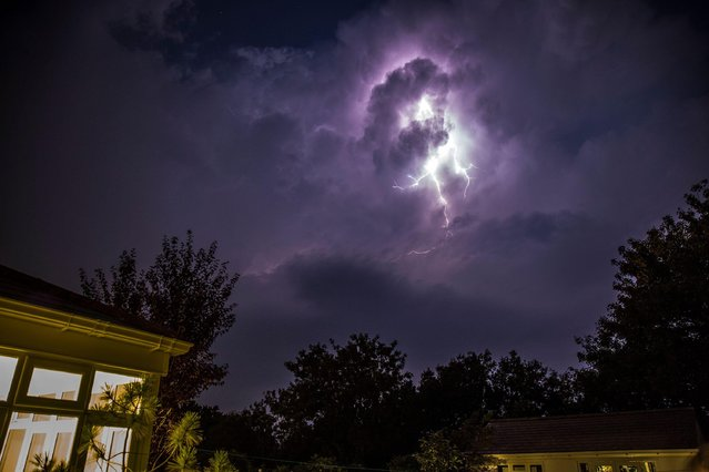 Lightning breaks dramatically through the clouds above the garden of a residential property in Kidderminster, UK as nighttime thunderstorms hit the county of Worcestershire on August 11, 2020. (Photo by Lee Hudson/Alamy Live News)