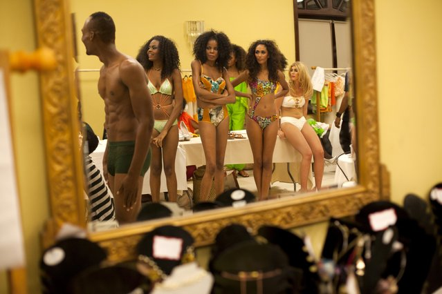 Models are reflected in a dressing room mirror wearing creations by designer Marly Clervin during Fashion Week in Port-au-Prince, Haiti, Friday, October 31, 2014. (Photo by Dieu Nalio Chery/AP Photo)