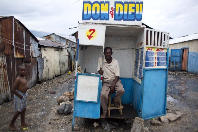 """Lottery vender Decidas Jean Rene sits in his kiosk baring the name """"Godsend"""" in the Cite Soleil slum of Port-au-Prince, Haiti, Monday, November 6, 2017. Customers can buy between 10 and 99 lottery numbers, spending a minimum of 5 Haitian gourdes, or about 7 U.S. cents, with the potential of winning $54 dollars. (Photo by Dieu Nalio Chery/AP Photo)"""