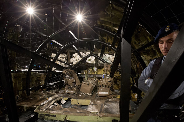 A Dutch Military Policeman guards part of the reconstructed cockpit, rear, and forward section of the fuselage after the Dutch Safety Board presented it's final report into what caused Malaysia Airlines Flight 17 to break up high over Eastern Ukraine last year, killing all 298 people on board, during a press conference in Gilze-Rijen, central Netherlands, Tuesday, October 13, 2015. (Photo by Peter Dejong/AP Photo)