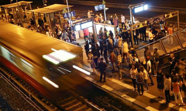 """People wait for trains at Warschauer Strasse station in Berlin, Germany, September 3, 2016. """"S-Bahn"""" and """"U-Bahn"""" trains run throughout the night in Berlin on weekends. They offer a way for thousands of party-lovers to move from club to club. (Photo by Hannibal Hanschke/Reuters)"""