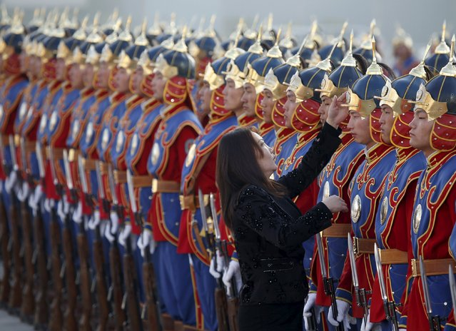 A woman adjusts the hat of a member of the honour guards before a welcoming ceremony for the visiting Germany's President Joachim Gauck outside the national parliament building at Sukhbaatar square, in Ulaanbaatar, Mongolia, October 15, 2015. (Photo by B. Rentsendorj/Reuters)