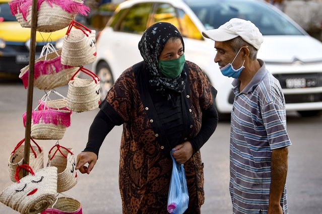 A Tunisian woman wearing a face mask for protection against the novel coronavirus speaks to a vendor at a market in the southwestern Tunisian town of Gabes on August 26, 2020, as cases of infection surge there. (Photo by Fethi Belaid/AFP Photo)