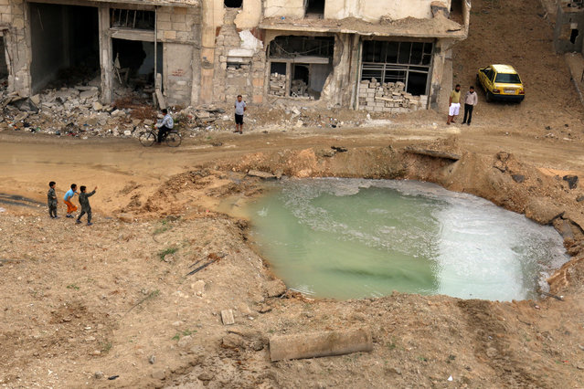 People inspect a hole in the ground filled with water in a damaged site after airstrikes on the rebel held Tariq al-Bab neighbourhood of Aleppo, Syria September 23, 2016. (Photo by Abdalrhman Ismail/Reuters)