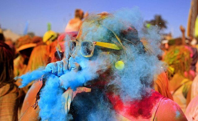 A woman blows blue paint powder on her friend during the Holi One Colour Festival in Cape Town, South Africa, March 2, 2013. (Photo by Schalk van Zuydam/Associated Press)