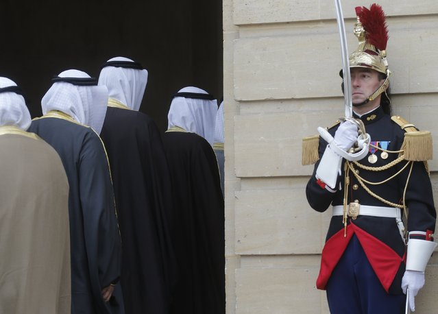 Members of Kuwait's delegation walk past a Republican Guard as they enter French Prime Minister's offices, the Hotel Matignon before a meeting in Paris, France, October 21, 2015. France signed on Wednesday 2.5 billion euros of defence deals and provisional agreements with Kuwait, including a sale of Airbus-built military helicopters worth 1 billion euros. (Photo by Christian Hartmann/Reuters)