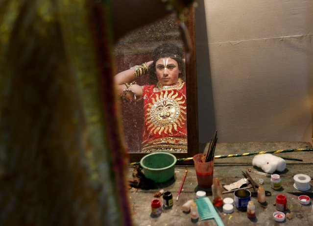 An artist is reflected in a mirror as he gets ready backstage before performing during Ramlila, a re-enactment of the life of Lord Rama, during Dussehra festival celebrations in Mumbai, India, October 22, 2015. Effigies of the 10-headed demon king Ravana are burnt on Dussehra, the Hindu festival that commemorates the triumph of Hindu god Rama over Ravana, marking the victory of good over evil. (Photo by Shailesh Andrade/Reuters)
