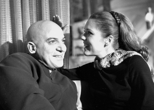 """British actress Diana Rigg strokes the head of U.S. actor Telly Savalas on the set of the new James Bond film """"On Her Majesty's Secret Service"""", at Pinewood Studios, England, January 13, 1968. (Photo by Bob Dear/AP Photo)"""