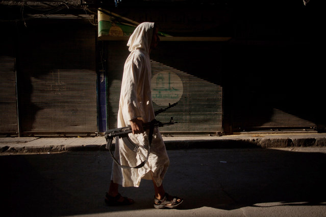 An FSA fighter walks through a street in the Bustan Al Qsar district in Aleppo, Syria, Wednesday, September 12, 2012. (Photo by Manu Brabo/AP Photo)