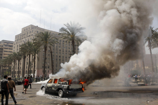 Egyptians extinguish a burning police vehicle, which has been set afire by angry protesters in Tahrir Square, once the epicenter of protests against former President Mubarak, in Cairo, Egypt, Monday, March 18, 2013. Egypt is currently mired in another wave of protests, clashes and unrest that have plagued the country since the ouster of authoritarian leader Hosni Mubarak in the pro-democracy uprising two years ago. (Photo by Amr Nabil/AP Photo)