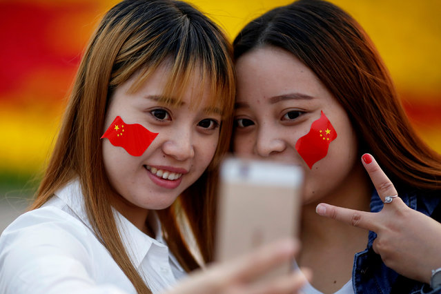 Girls wearing Chinese flags on their cheeks take pictures as people gather in Tiananmen Square to celebrate National Day marking the 67th anniversary of the founding of the People's Republic of China, in Beijing October 1, 2016. (Photo by Damir Sagolj/Reuters)