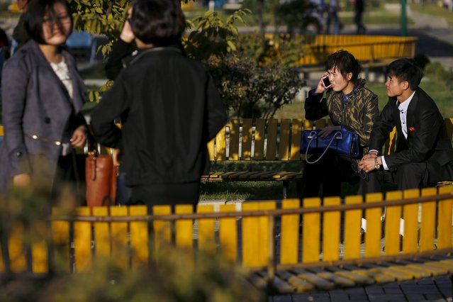People enjoy nice weather at a park in front of the Pothonggang Department Store in central Pyongyang October 11, 2015. (Photo by Damir Sagolj/Reuters)
