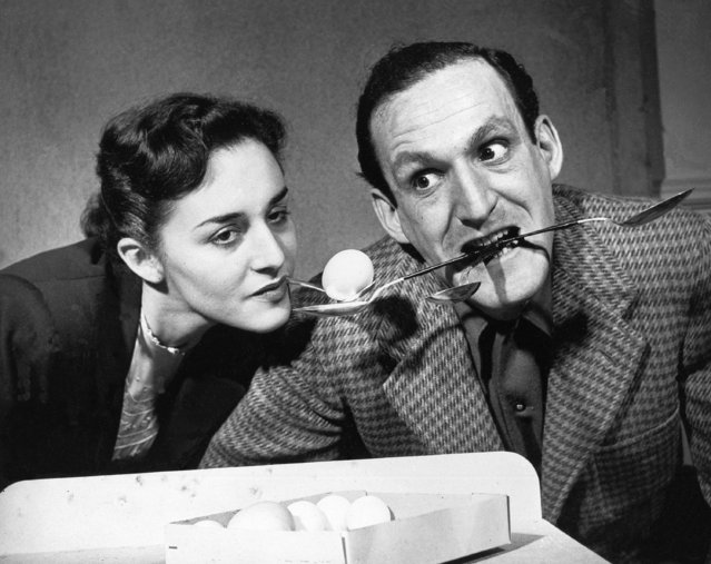 """A woman tries to pick three eggs from a box and transfer them to the three spoons held in her partner's mouth in a stunt arranged for the """"Beat The Clock"""" television show in New York, March 8, 1952. (Photo by AP Photo)"""