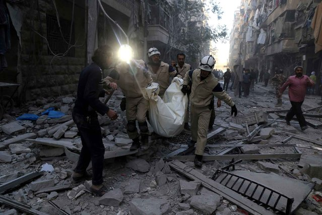 Syrian emergency personnel carry a body following an air strike on November 3, 2015, in the rebel-held side of the northern city of Aleppo. (Photo by Baraa Al-Halabi/AFP Photo)