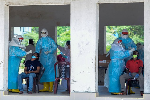 Medical workers collect swab samples from residents to test for the COVID-19 coronavirus in Colombo on November 5, 2020. (Photo by Lakruwan Wanniarachchi/AFP Photo)