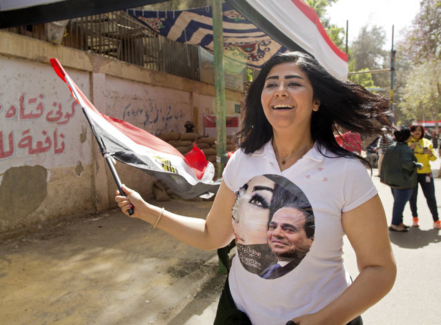 Fatma Mounir, a supporter of President Abdel-Fattah el-Sissi, wears a T-shirt with his picture as she chants national songs in front of a polling station during the first day of voting, in Cairo, Egypt, Monday, March 26, 2018. Polls opened on Monday in Egypt's presidential election with the outcome – a second, four-year term for President Abdel-Fattah el-Sissi – a foregone conclusion, in what is seen by critics as a signal of the country's return to the authoritarian rule that prevailed since the 1950s. (Photo by Amr Nabil/AP Photo)