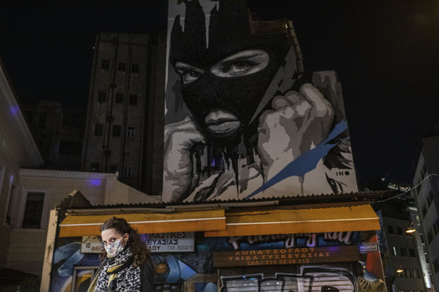 A woman wearing a face mask to curb the coronavirus walks in front of a mural created by street artist INO in the Psiri district of Athens, on Friday, October 23, 2020. (Photo by Petros Giannakouris/AP Photo)