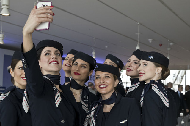 Aegean airlines air hostesses take selfies after a news conference in Athens, Wednesday, March 28, 2018. (Photo by Petros Giannakouris/AP Photo)