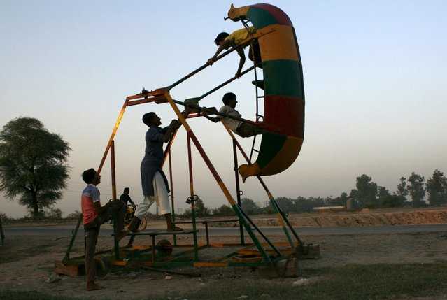 Children play on a swing in the village of Chack Rasala outside Faisalabad, Pakistan October 9, 2015. (Photo by Fayyaz Hussain/Reuters)