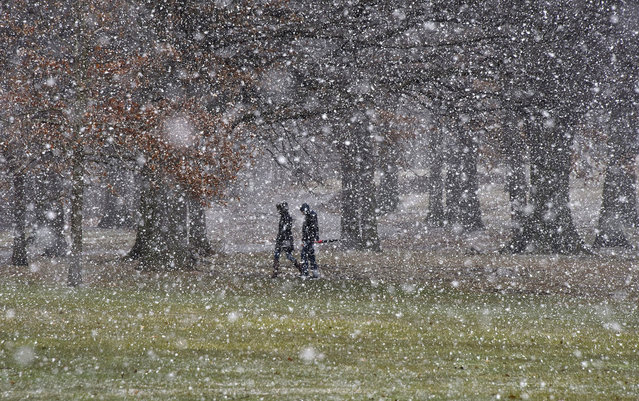 People cross Flagstaff Hill as the snow starts to fall, in Schenley Park, on their way to the Carnegie Mellon University campus, Tuesday, March 20, 2018, in the Oakland section of Pittsburgh. Yet another powerful storm bore down on the Northeast on Tuesday, with wind-whipped snow falling in parts of Pennsylvania and New Jersey as people grumbled and complained about a first day of spring that looked an awful lot like the last weeks of winter. (Photo by Darrell Sapp/Pittsburgh Post-Gazette via AP Photo)