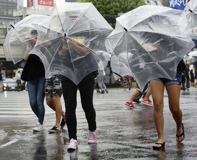Pedestrians walk under heavy rain and wind in Tokyo, Japan, in this photo taken by Kyodo August 22, 2016. (Photo by Reuters/Kyodo News)