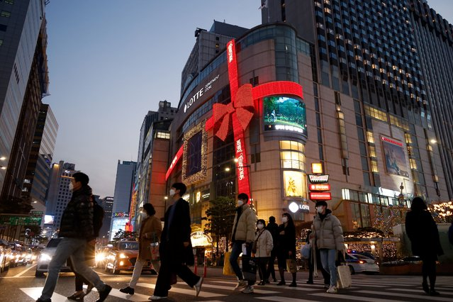 People walk on a zebra crossing in front of a department store in Christmas season themed decorations amid the coronavirus disease (COVID-19) pandemic in Seoul, South Korea, November 26, 2020. (Photo by Kim Hong-Ji/Reuters)