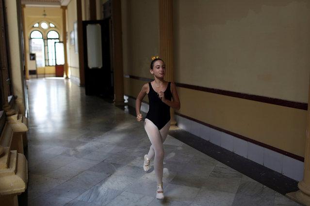 A student at the Cuba's National Ballet School (ENB) runs to a classroom in Havana, Cuba, October 12, 2016. (Photo by Alexandre Meneghini/Reuters)
