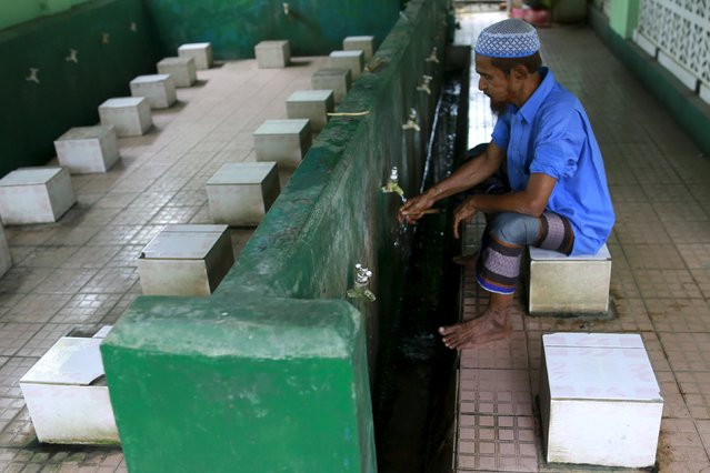 A Muslim Rohingya man washes his hands before praying at a mosque in Aung Minglar in Sittwe October 29, 2015. (Photo by Soe Zeya Tun/Reuters)