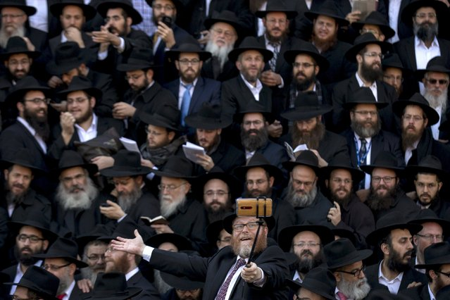 Rabbis gather to pose for a group photo in front of the Chabad-Lubavitch world headquarters in the Brooklyn borough of New York November 8, 2015. Some 4,400 Chabad-Lubavitch Hasidic rabbis from around the world gathered for the annual International Conference of Chabad-Lubavitch Emissaries. (Photo by Brendan McDermid/Reuters)