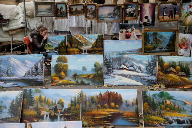 A street vendor selling paintings drinks hot tea while waiting for customers on a sidewalk in central Lviv, Ukraine, October 20, 2016. Picture taken October 20, 2016. (Photo by Gleb Garanich/Reuters)