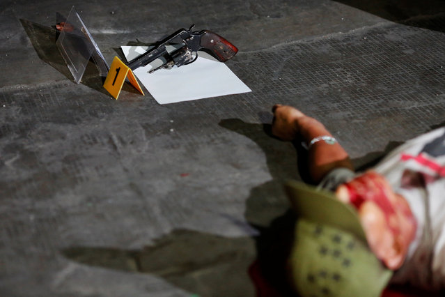 A gun is seen next to the body of a man was killed in a shootout with police in Manila, Philippines early October 21, 2016. According to the police, sachets containing substance believed to be drug shabu (Methamphetamine Hydrochloride) were found in the killed man's pockets. (Photo by Damir Sagolj/Reuters)