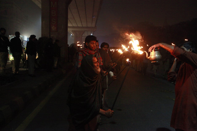 A man gets his torch filled with oil during a rally to celebrate Eid-e-Milad-ul-Nabi, the birth anniversary of Prophet Mohammad, in Lahore January 3, 2015. (Photo by Mohsin Raza/Reuters)