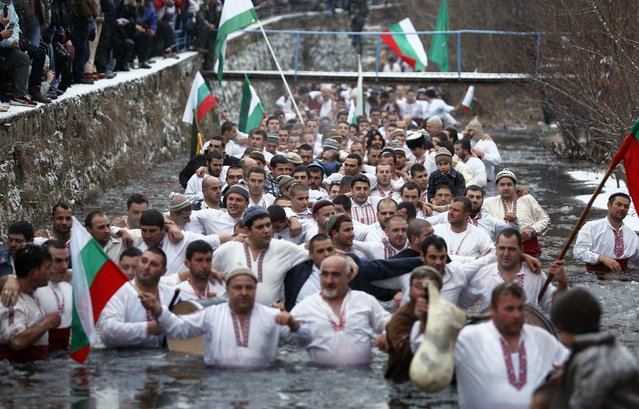 Bulgarian men dance and sing in the icy waters of the Tundzha river during a celebration to commemorate Epiphany Day in the town of Kalofer January 6, 2015. (Photo by Stoyan Nenov/Reuters)