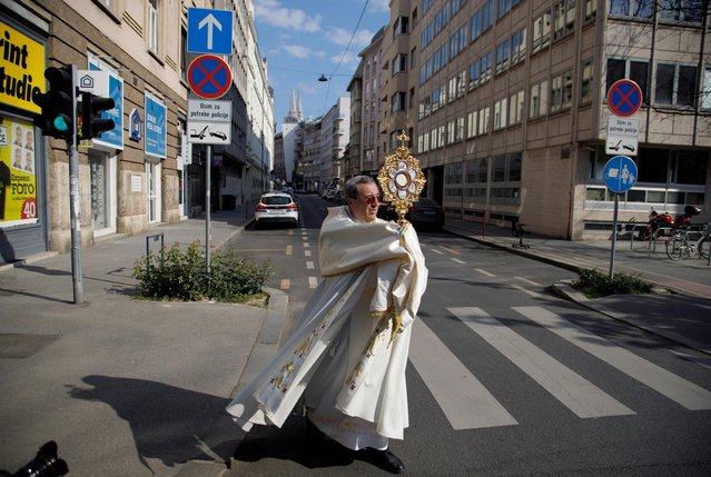 Priest Ivan Matic walks with a cross and blesses believers during Easter, amid the coronavirus disease (COVID-19) outbreak and in the aftermath of the earthquake that hit the country on March 22, in Zagreb, Croatia on April 12, 2020. (Photo by Antonio Bronic/Reuters)