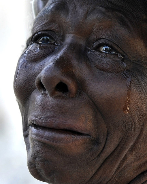 """In this January 2010 photo submitted by the Washington Post tilted """"Haiti Weeps"""" a woman cried while attending a worship service at Cathedral Notre Dame, which was destroyed in the quake in Port-au-Prince. (Photo by Carol Guzy/AP Photo/The Washington Post)"""