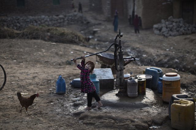 An Afghan refugee child pumps water from a well, while waiting her elder sister in a slum on the outskirts of Islamabad, Pakistan, Sunday, January 11, 2015. (Photo by Muhammed Muheisen/AP Photo)