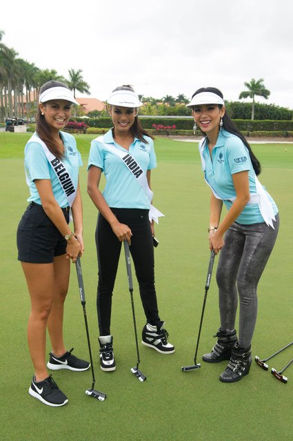 This picture provided by the Miss Universe Organization shows Anissa Blondin, Miss Belgium 2014; Noyonita Lodh, Miss India 2014; and Elvira Devinamira, Miss Indonesia 2014; getting ready for the OPTX Eyewear putting contest at Trump National Doral Miami on January 12, 2015 in Florida. (Photo by AFP Photo/Miss Universe Organization)