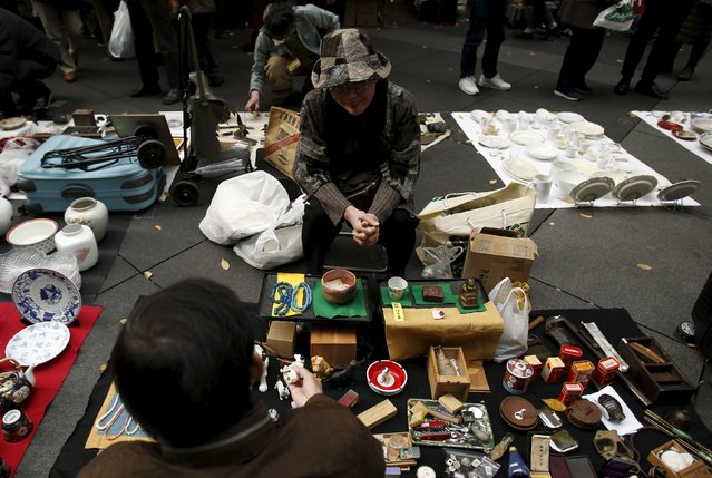 A shop clerk chats with a customer at a flea market at a shopping district in Tokyo, Japan, December 6, 2015. (Photo by Yuya Shino/Reuters)