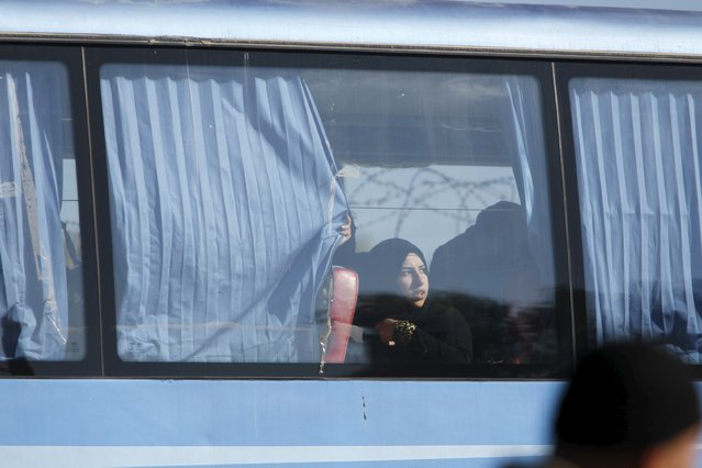 A woman looks out of the window in a bus as she leaves district of Waer during a truce between the government and rebels, in Homs December 9, 2015. Scores of people left the last area held by insurgents in the Syrian city of Homs on Wednesday under a local truce between the government and rebels, a monitoring group said, a rare agreement in Syria's nearly five-year conflict. (Photo by Omar Sanadiki/Reuters)