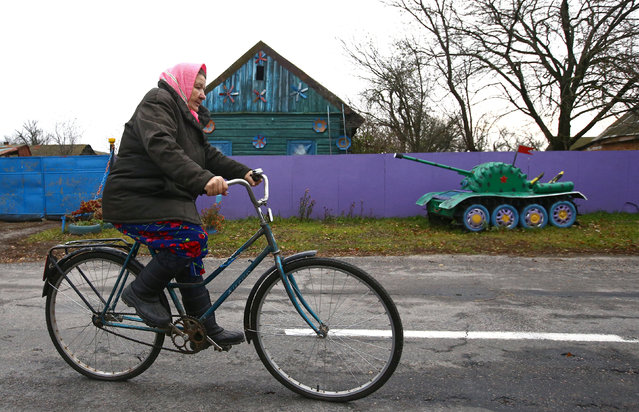 A woman rides a bicycle in front of an installation with a small copy of a tank at a villager's house in the village of Vits, Belarus November 8, 2016. (Photo by Vasily Fedosenko/Reuters)