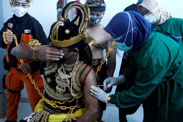 """An Indonesian healthcare worker injects a dose of Sinovac's vaccine to a man dressed in Indonesia's traditional human puppet costume known as """"Wayang"""", as Indonesia drives mass vaccination for the coronavirus disease (COVID-19), at a hospital in Solo, Central Java province, Indonesia, January 22, 2021. This action is to provide support for the government's COVID-19 vaccination program using a safe vaccine. (Photo by Maulana Surya/Antara Foto via Reuters)"""