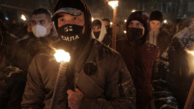 Bulgarian far-right nationalists hold torches as they gather in the country's capital, to honour a World War II general known for his anti-Semitic and pro-Nazi activities, in Sofia, Saturday, February 13, 2021. Braving sub-zero temperatures, hundreds of dark-clad supporters of the Bulgarian National Union group flocked to a central square where they had planned to kick off the annual Lukov March, a torch-lit procession held every February to the former house of Gen. Hristo Lukov. (Photo by Valentina Petrova/AP Photo)