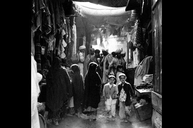 Afghan boys, men, and women, some in bare feet, shop at a marketplace in Kabul, Afghanistan, in May of 1964. (Photo by AP Photo via The Atlantic)