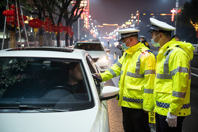 Traffic police officers are on duty to ensure traffic rules compliance during the Spring Festival holiday, in southeast China's Fujian Province, February 11, 2021. (Photo by CFP/China Stringer Network)