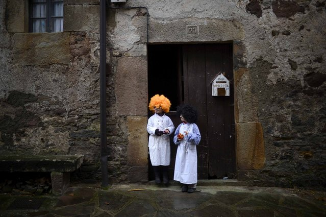Children wearing wigs stand in a doorway during carnival celebrations in Zubieta January 27, 2015. (Photo by Vincent West/Reuters)