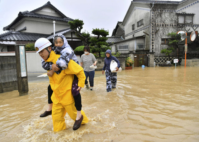 Residents are evacuated to a safer place from floodwaters caused by heavy rains in Kurashiki, Okayama prefecture, southwestern Japan, Saturday, July 7, 2018. Torrents of rainfall and flooding continued to batter southwestern Japan. (Photo by Koki Sengoku/Kyodo News via AP Photo)