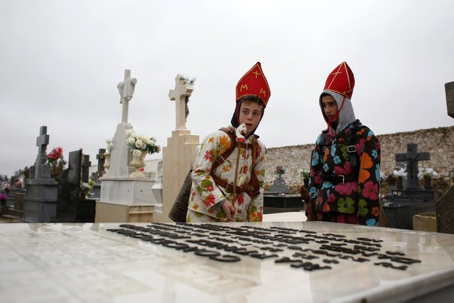 """Young believers dressed as """"diablos"""" (devils) stand by a tombstone at the cemetery during the """"Endiablada"""" festival in Almonacid del Marquesado, in central Spain February 2, 2015. (Photo by Susana Vera/Reuters)"""