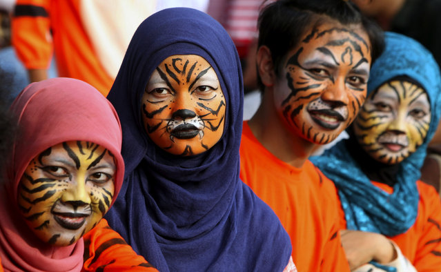 Activists with faces painted to resemble tigers, take part in a protest against Sumatran tiger trade that marks the Global Tiger Day, in Jakarta, Indonesia, Monday, July 29, 2013. Sumatran tiger is the world's most critically endangered tiger subspecies with fewer than 400 remain in the wild and may become extinct in the next decade due to poaching and habitat loss. (Photo by Tatan Syuflana/AP Photo)