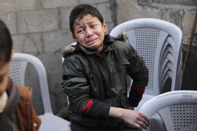 A Palestinian boy weeps during the funeral of Hani Wahdan, 22, at his family house in Gaza City, Saturday, December 26, 2015. Palestinian Health Ministry spokesman Ashraf al-Kidra says, Wahdan was killed Friday during clashes with Israeli soldiers on the Israeli border with east of Gaza City. (Photo by Adel Hana/AP Photo)