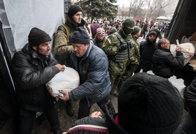 Local residents unload a truck of humanitarian aid near Ukrainian servicemen in Debaltseve, eastern Ukraine, February 6, 2015. (Photo by Gleb Garanich/Reuters)